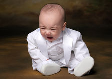 Tux sad. Upset baby boy in white tuxedo crying in studio Royalty Free Stock Photography