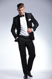 Tuxedo man poses with hand on jacket and in pocket stock photo