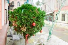 Tuya in de vorm van een bal is verfraaid als Nieuwjaarverbinding met rood ballen en boomspeelgoed op de straat en de stad stock foto's