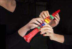 Tuyau coloré et quatre mains de femme le prenant photos stock