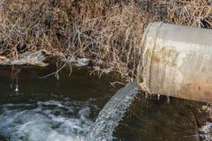 Tuyau concret transportant l'eau polluée dedans à un petit étang photos stock