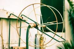 Tuyau de jardin arrosant la roue au jet photo libre de droits