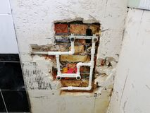 Tuyau et portes de propylène dans un mur de briques - soudure de propylène photo stock