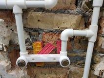 Tuyau et portes de propylène dans un mur de briques - soudure de propylène images stock