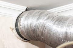 Tuyau ondul? en aluminium m?tallique expansible de ventilation de climatisation dans la cuisine reliant un capot de cuiseur et un photographie stock