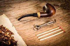 Tuyau, tabac, papier et matchs sur une table en bois Photos libres de droits