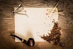Tuyau, tabac, papier et matchs sur une table en bois Photos stock