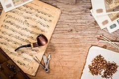 Tuyau, tabac, vieil argent et notes Photographie stock