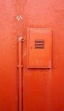 Tuyau vertical en métal et boîte électrique sur le mur orange de couleur Photographie stock