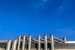 Tuyaux en métal d'un bâtiment contre le ciel bleu vif image stock