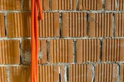 Tuyaux en plastique oranges pendant du mur de briques Images stock