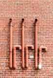 Tuyaux rouges sur le mur de briques rouge Image libre de droits