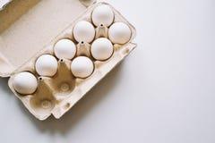 Tuzin jajek w kartonowym zbiorniku na bielu zdjęcia royalty free
