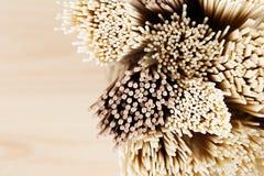 Tvärsnittet av olika packar av rå nudlar stänger sig upp på det mjuka beigea träbrädet, bästa sikt Arkivfoton