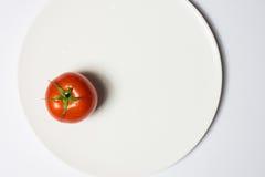 Tvättad mogen tomat på plattan på vit bakgrund, horisontalimag royaltyfri foto