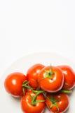 Tvättad mogen tomatgrupp på plattan på vit bakgrund, vertica royaltyfria foton