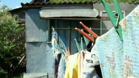 Tvättad tillfällig kläder och olik linne som hänger på en klädstreck i trädgård arkivfilmer