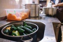 Tvättade nytt gurkor i en kastrull i köket i vasken Förberedelse av produkter för att laga mat royaltyfria bilder