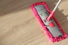 Tvättande damm på trägolv med golvmopp royaltyfri foto