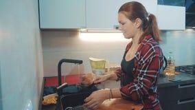 Tvättande disk för flicka i kökskärbrädan Kvinnakockar i köket flickan tvättar en kniv på i vasken under arkivbilder