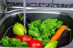 Tvättande grönsaker för att laga mat, vegetarisk mat royaltyfria foton