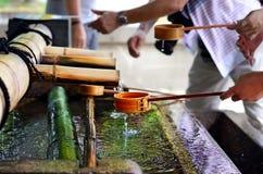 Tvättande händer för folk, Yasaka Jinja, Kyoto, Japan royaltyfri bild