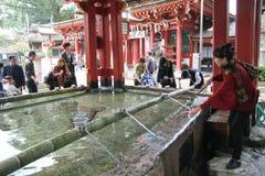 Tvättande hand för folk med det heliga vattnet som är främst av den Dazaifu tenmanguen Arkivfoton