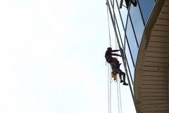 Tvättar industriell klättrare två fönsteraffär arkivfoto