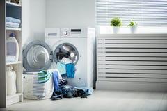 Tvätteri En tvagningmaskin och en hög av smutsig kläder Arkivfoto