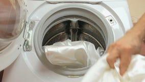 Tvätteri Mannen sätter vit linne i tvagningmaskinen Closeuphand stock video