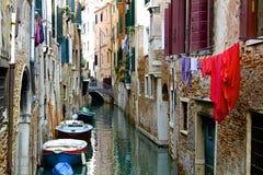 Tvätteri och fartyg på den Venetian kanalen fotografering för bildbyråer