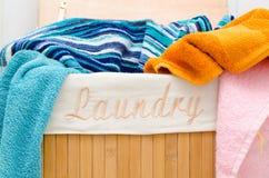 Tvättkorg med handdukar arkivbild