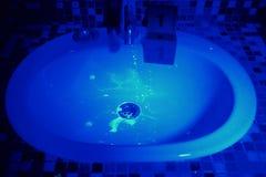 Tvättställ i badrum under UV ljus Royaltyfri Foto