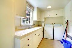 Tvättstuga med vita gamla kabinetter i stort historiskt hem. Arkivbild