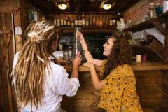 Två ägare av bar som har gyckel, medan sätta exponeringsglas på stång, står arkivfoto