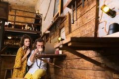 Två ägare av liten bar som tillsammans dricker något te och arbete royaltyfria foton