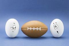 Två ägg ser med den konstiga framsidan till en ballong av rugby Royaltyfri Foto