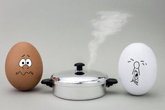 Två ägg ser med den konstiga framsidan till en varm kruka som ska lagas mat Arkivbild