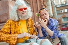Två äldre flower-power-folket som tycker om deras gatakapacitet Fotografering för Bildbyråer