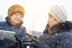 Två äldre kvinnor försöker att figurera ut plattan Arkivbild