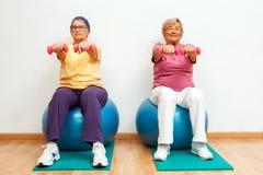 Två äldre kvinnor som gör muskeln, övar med vikter i idrottshall Arkivbilder