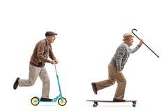 Två äldre män med en av dem som rider en sparkcykel och annan Arkivfoton