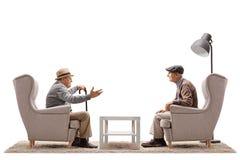 Två äldre män som placeras i fåtöljer som har en konversation arkivfoto