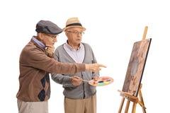 Två äldre män som ser en målning och ett samtal arkivfoto
