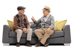 Två äldre män som sitter på en soffa och ett samtal royaltyfri bild