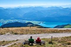 Två äldre personer sitter på en bänk och en blick på sjön Wolfgangsee Salzkammergut region, fj?ll?ngar, ?sterrike arkivfoton