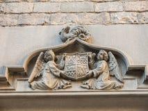 Två änglar rymmer en forntida sköld av Barcelona, som innehåller frimurar- symboler, på en drake Dörr av kloster av San Agustín arkivfoto