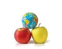 Två äpplen och ett litet jordklot Fotografering för Bildbyråer