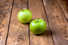 Två äpplen på en träbakgrund Arkivbild