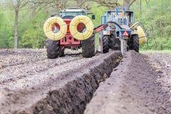 Två åkerbruka traktorer som gräver dräneringrör i jordning Arkivfoto